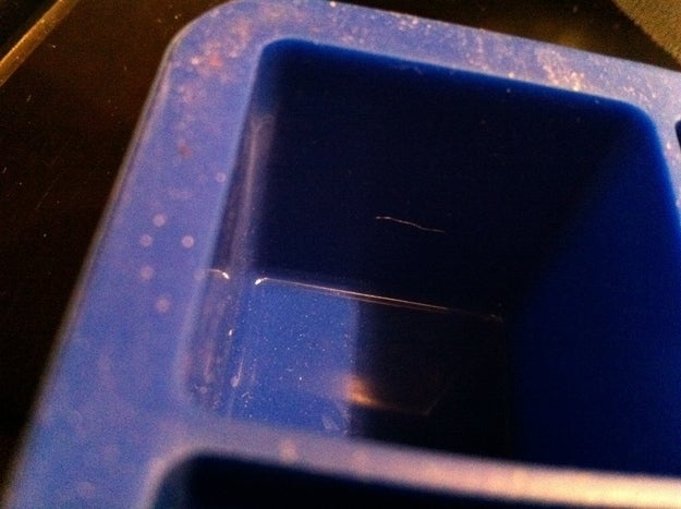 Most you can just dump in the dishwasher, but if you use silicone trays you may have a problem with calcium sulfate buildup. A vinegar and water soak should help you out.