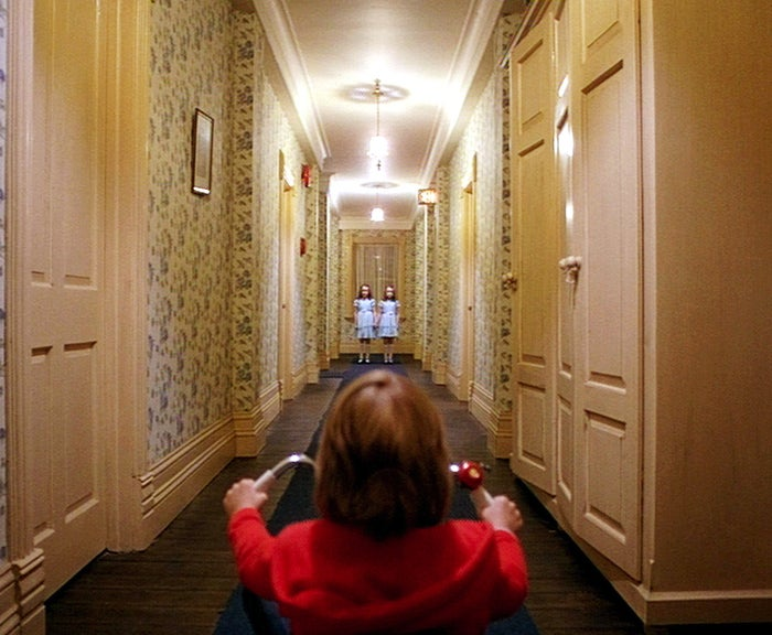 """In the film, we're told that the previous caretaker of The Overlook hotel, named Grady, killed his two young daughters. So naturally, when we see two creepy girls staring at young Danny — and then a quick, horrifying shot of their bloody bodies in that same hallway — we assume they're the Grady girls. Not so, says The Shining obsessive Rob Ager! A hotel exec tells Danny's father Jack (Jack Nicholson) that the girls were """"about eight and ten"""" — ergo, not twins. So who are the girls? Are they mirrored projections of Danny's subconscious? Are they Danny and his imaginary """"friend"""" Tony? Or are they perhaps Danny's mother Wendy (Shelley Duvall) as a young girl? Obsess away!"""