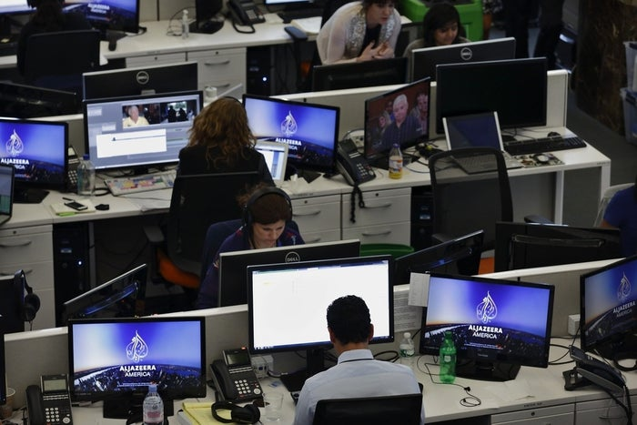Journalists work in the newsroom at the Al Jazeera America broadcast center, where the network launched Tuesday with a lengthy segment on climate change.