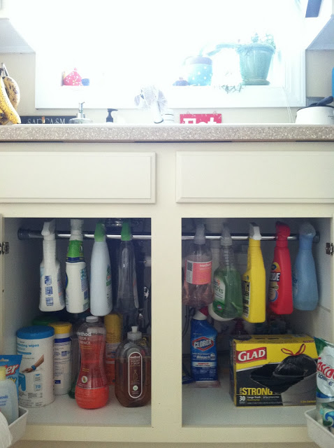 Hang cleaning products under the sink with a tension rod.