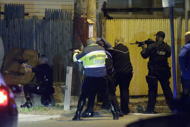 Police officers aim their weapons in Watertown, Mass., early Friday morning.