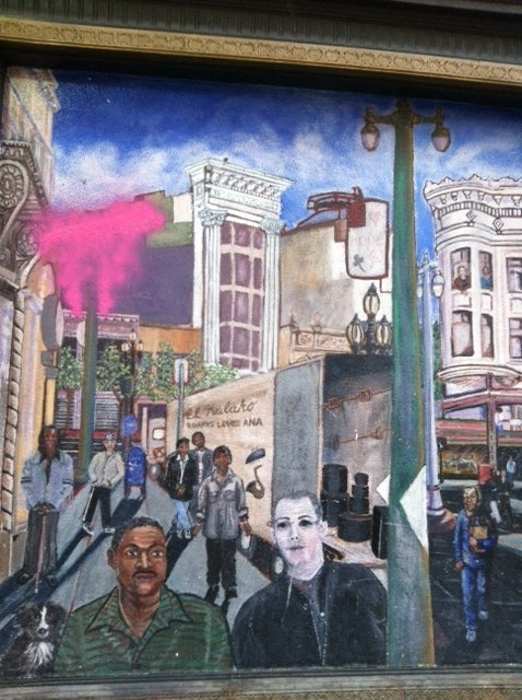 A mural on the Warfield building, Spotify's new home, depicts the Mid-Market street life.