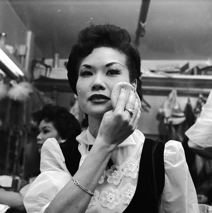 A chorus girl at the Forbidden City nightclub adds the finishing touches to her makeup.