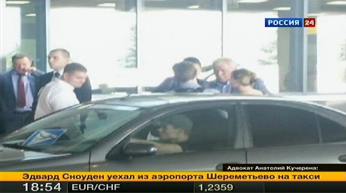 Edward Snowden talks with Russian lawyer Anatoly Kucherena (2nd R) in front of a car at Moscow's Sheremetyevo on Thursday.