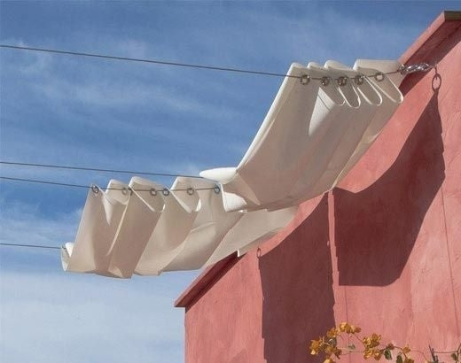 Attach one side to the house and the other side to a pole or tree, then slide the curtains across for shade.