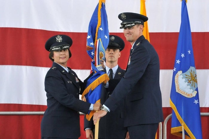 Maj. Gen. Sandra Finan, Air Force Nuclear Weapons Center commander, passes the guidon to Col. Tom Miller, new 377th Air Base Wing and installation commander, at a change of command ceremony July 11.