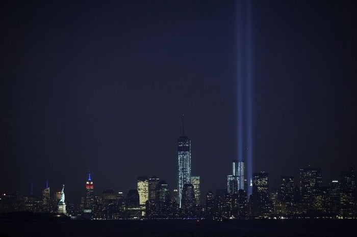 The Tribute in Light is seen from the Tear Drop Memorial park in Bayonne, New Jersey. On the left is the Statue of Liberty and the Empire State Building lit up in red, white and blue.