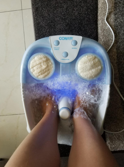 person's feet in the foot spa