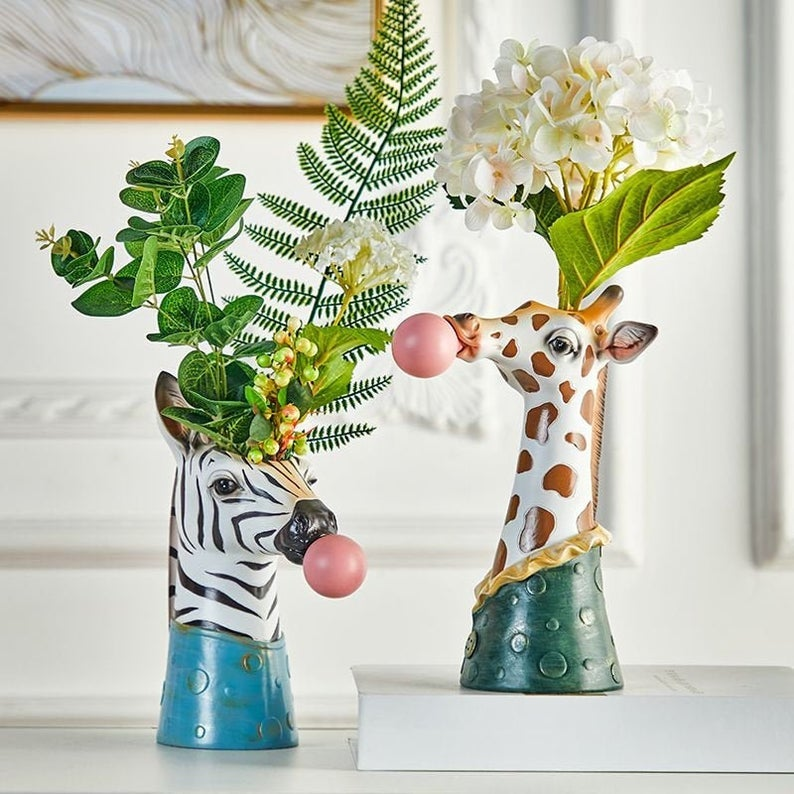 the tall skinny vases shaped like zebra and giraffe heads with a large pink bubble coming out of their mouths, filled with plants