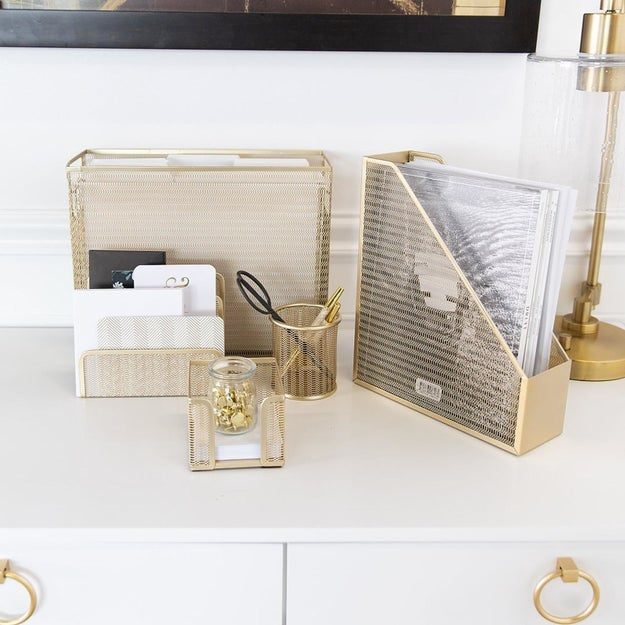 Five gold desk organizers filled with supplies and placed on desk