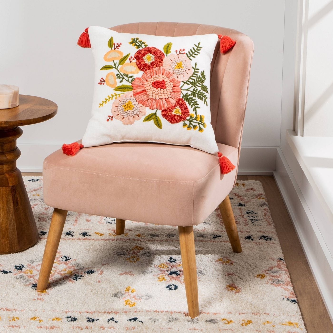 square white pillow with embroidered pink and red flowers and red tassels in each corner
