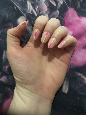 writer's hand with oval shaped light pink fake nails with neon stripes down the middle