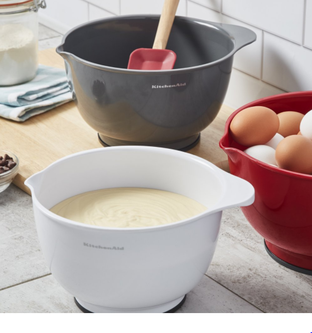 Grey, white, and red mixing bowels with KitchenAid written on them. The white bowl is filled with batter.