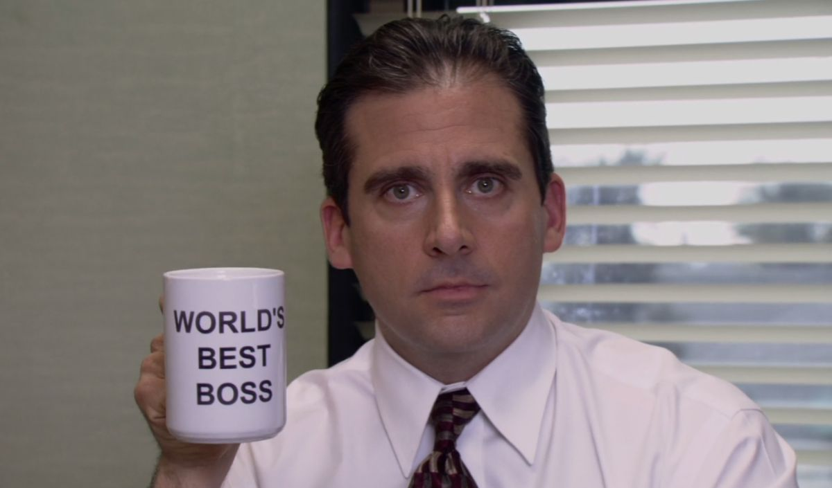 "Michael Scott is sitting at a desk holding up a mug that reads, ""World's best boss"""