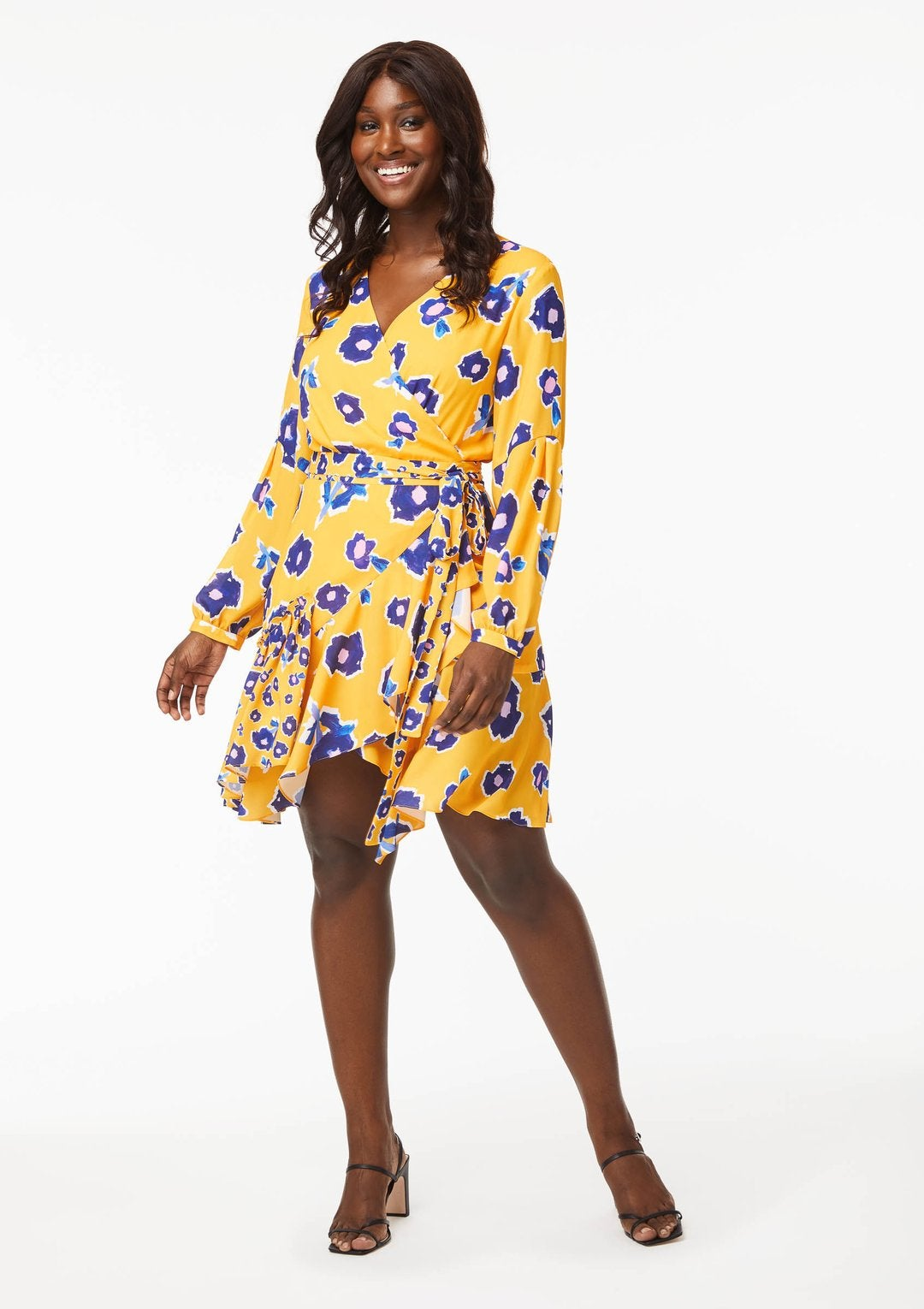 Model wearing yellow-gold dress with blue flowers on it