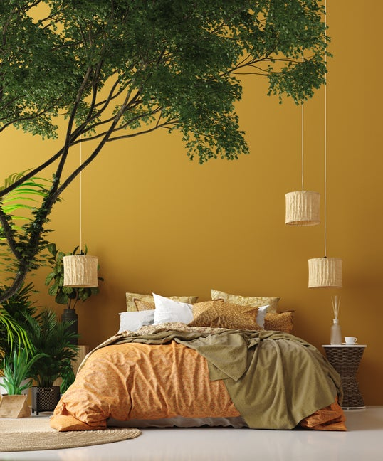 A jungle-inspired bedroom with an unmade bed close to the tile floor and a huge plant hanging over the top of the bed