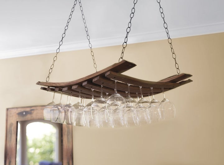 the wood panel hanging from chains and holding stemware between the slats