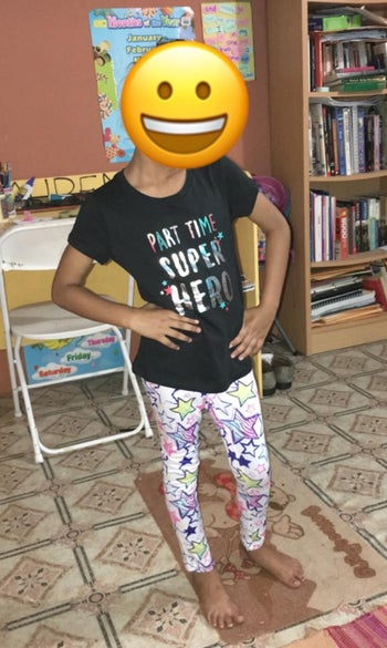 a reviewer's child with their face covered with an emoji, wearing one of the tees
