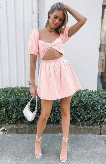 model in pale pink short puff sleeve dress with large waist cutout
