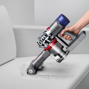a model using the dyson vacuum to clean a couch