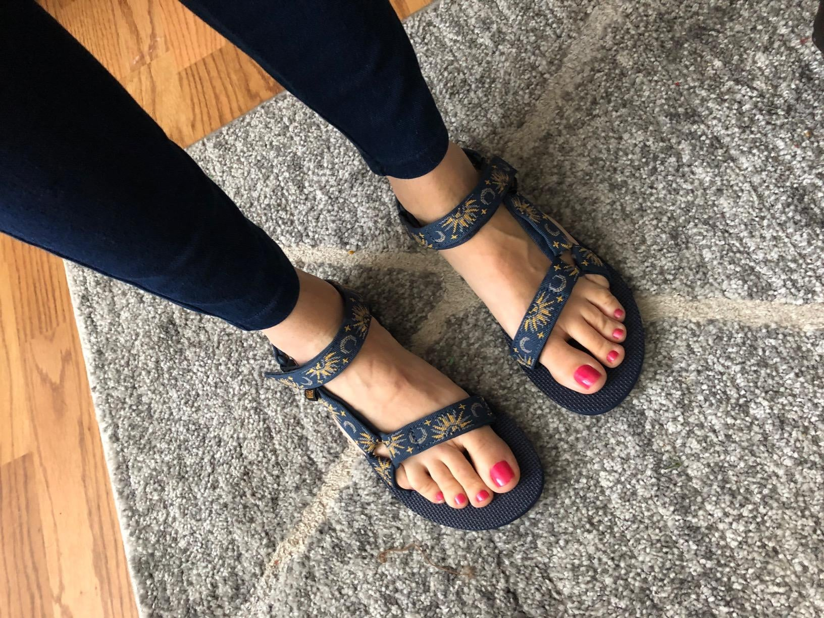 a reviewer wearing tevas strappy sandals with a moon and sun pattern on them