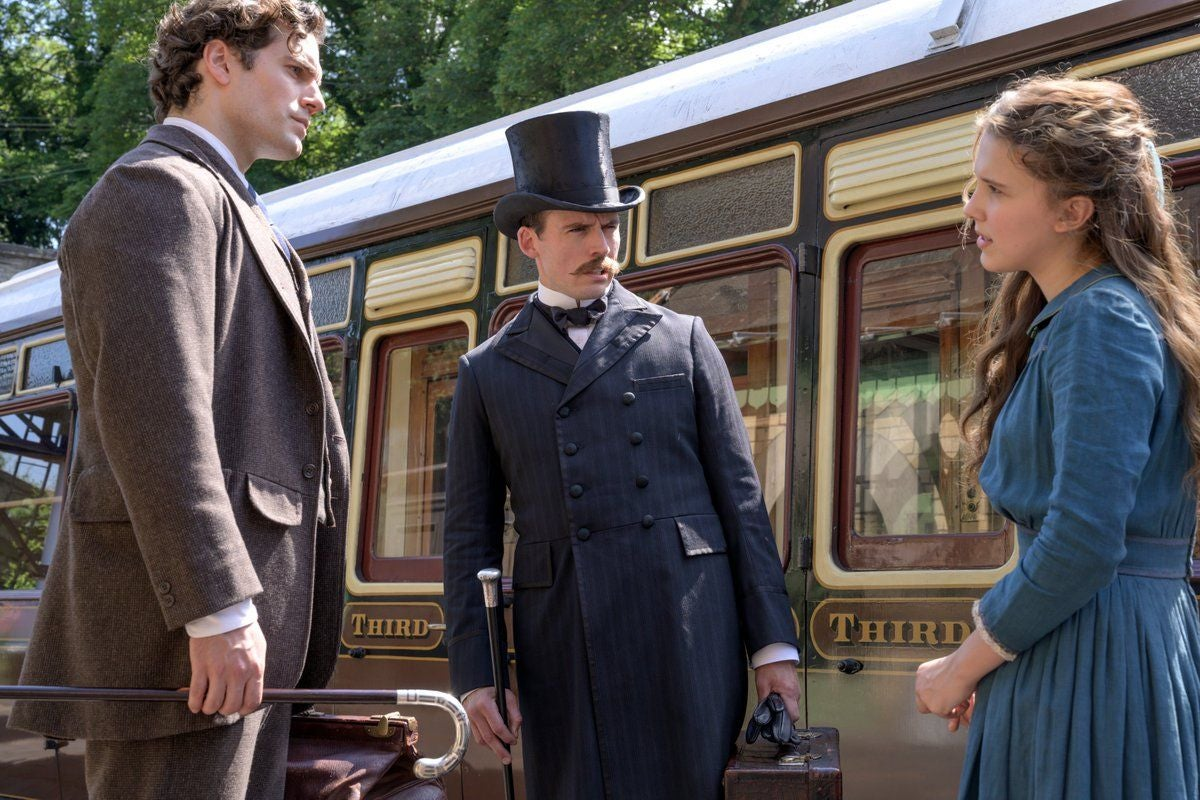 Enola speaks with Sherlock and Mycroft at the train station