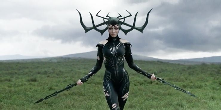 woman in a tight bodysuit holds two swords while walking through a field