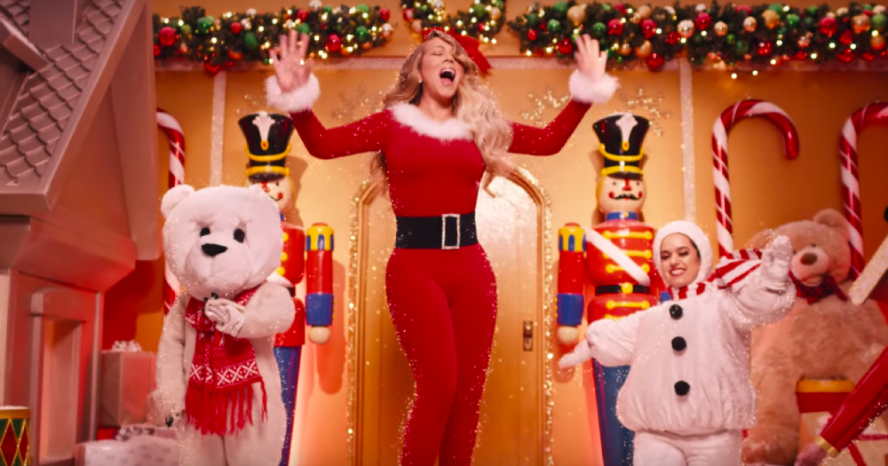 Mariah Carey is dressed in a Santa suit while surrounded by Christmas characters
