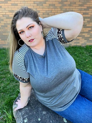 reviewer wearing the top in gray with striped and leopard print sleeves