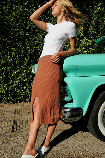 a model in a burnt orange midi skirt with a slit