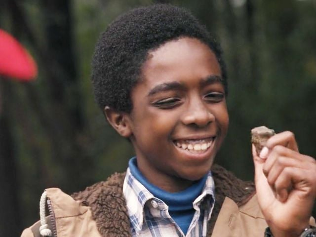 Lucas is outdoors smiling, with a small rock in his hand