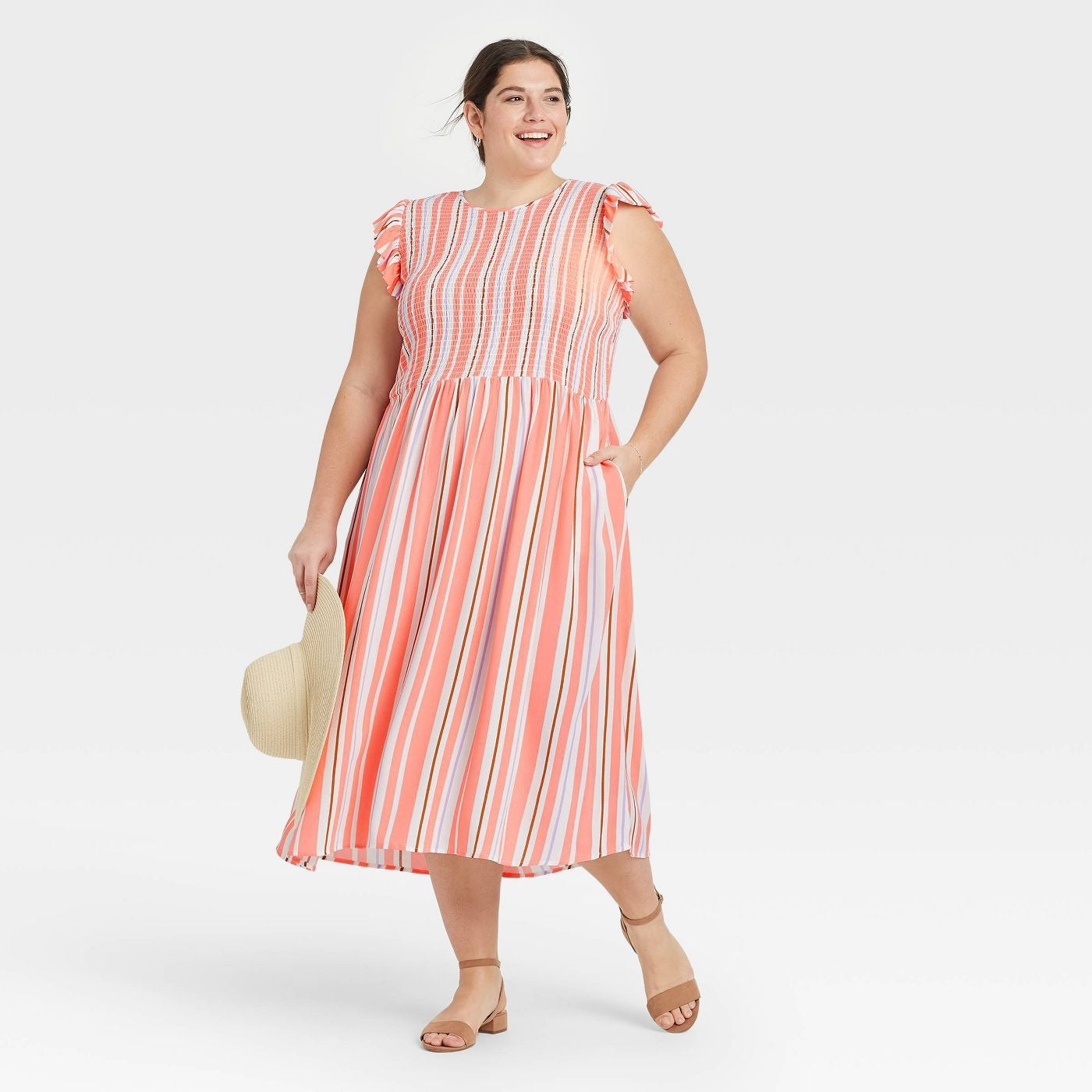 model in the coral, white, brown, and lilac vertical stripe sleeveless dress with ruffle detail