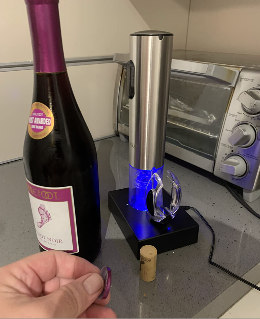 reviewer image of cylinder shaped blue lit opener on black base next to an uncorked wine bottle