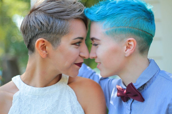 Two women with very short haircuts look deep into one another's eyes