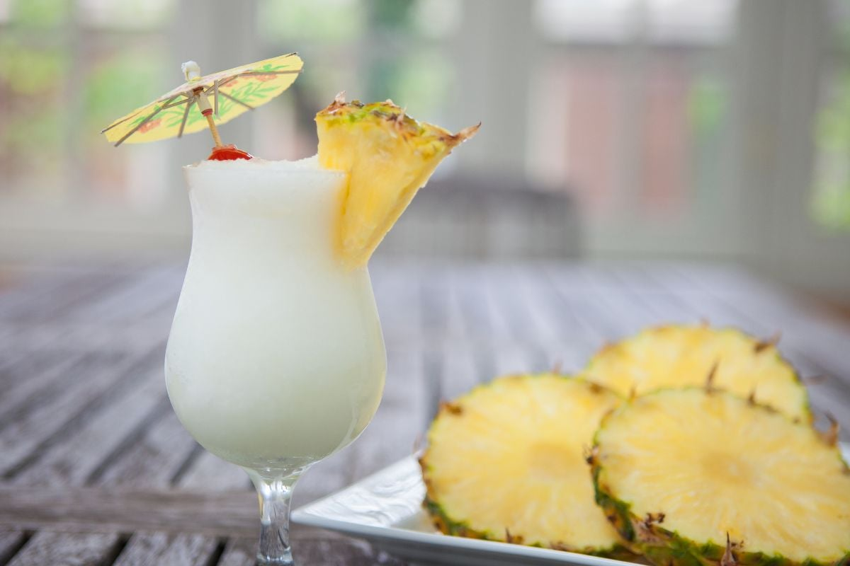 A white cocktail with an umbrella on a wooden table beside some pineapple slices