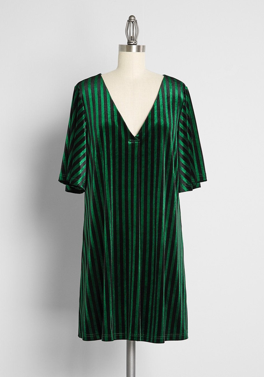 a green dress with flutter sleeves and vertical green and black stripes