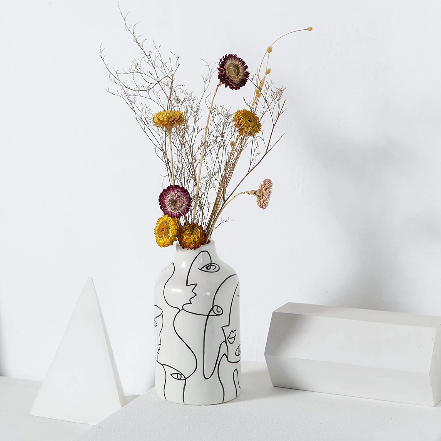 a white vase with abstract faces outlined on it in black