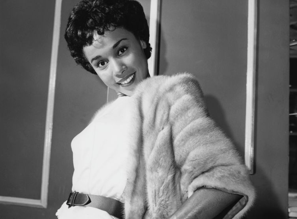 A woman with short hair is smiling at the camera while leaning against a wall. She wears a cotton dress with a leather belt over it, and an elbow-length fur jacket
