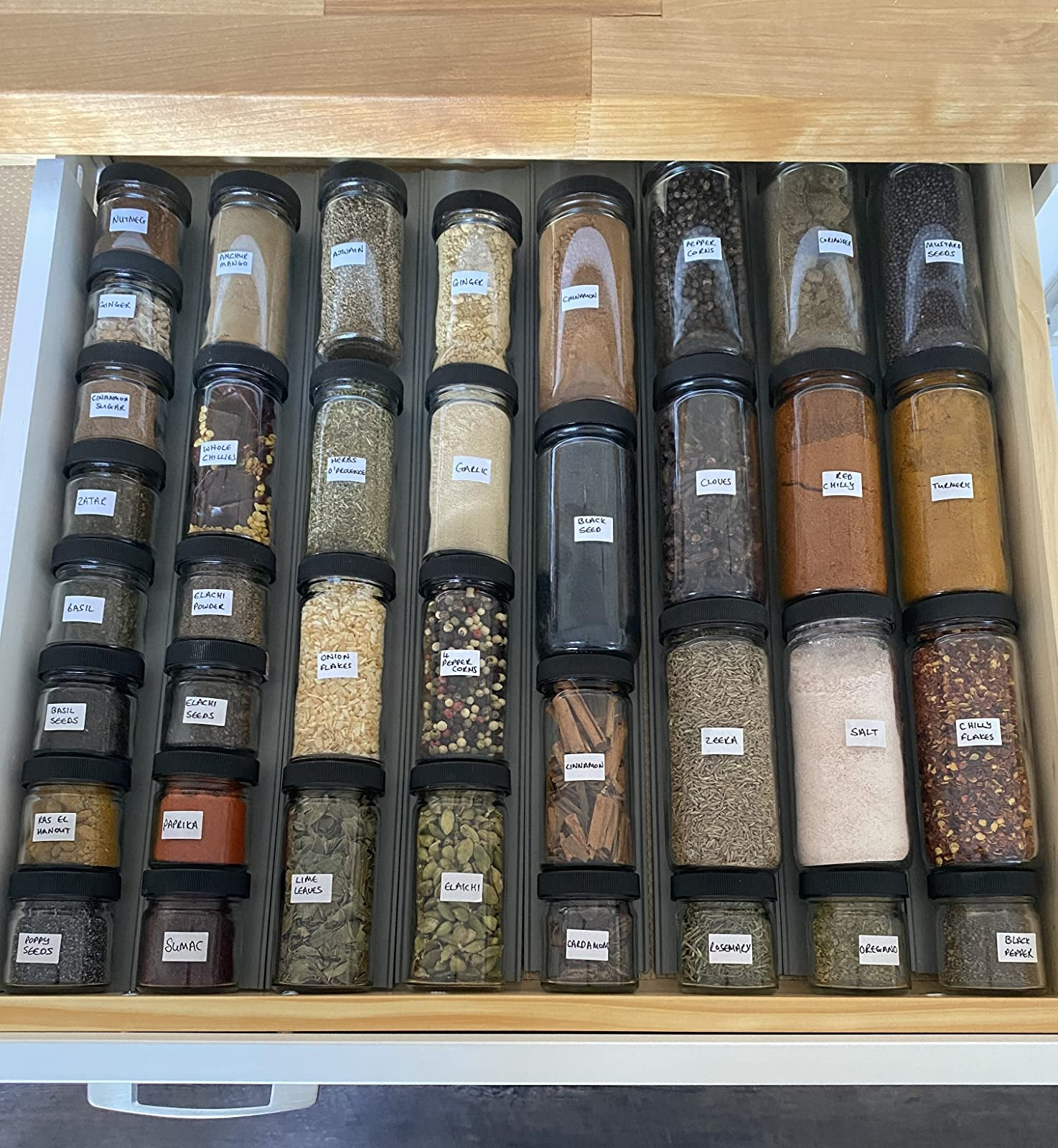 A reviewer's spice bottles neatly lined in a drawer
