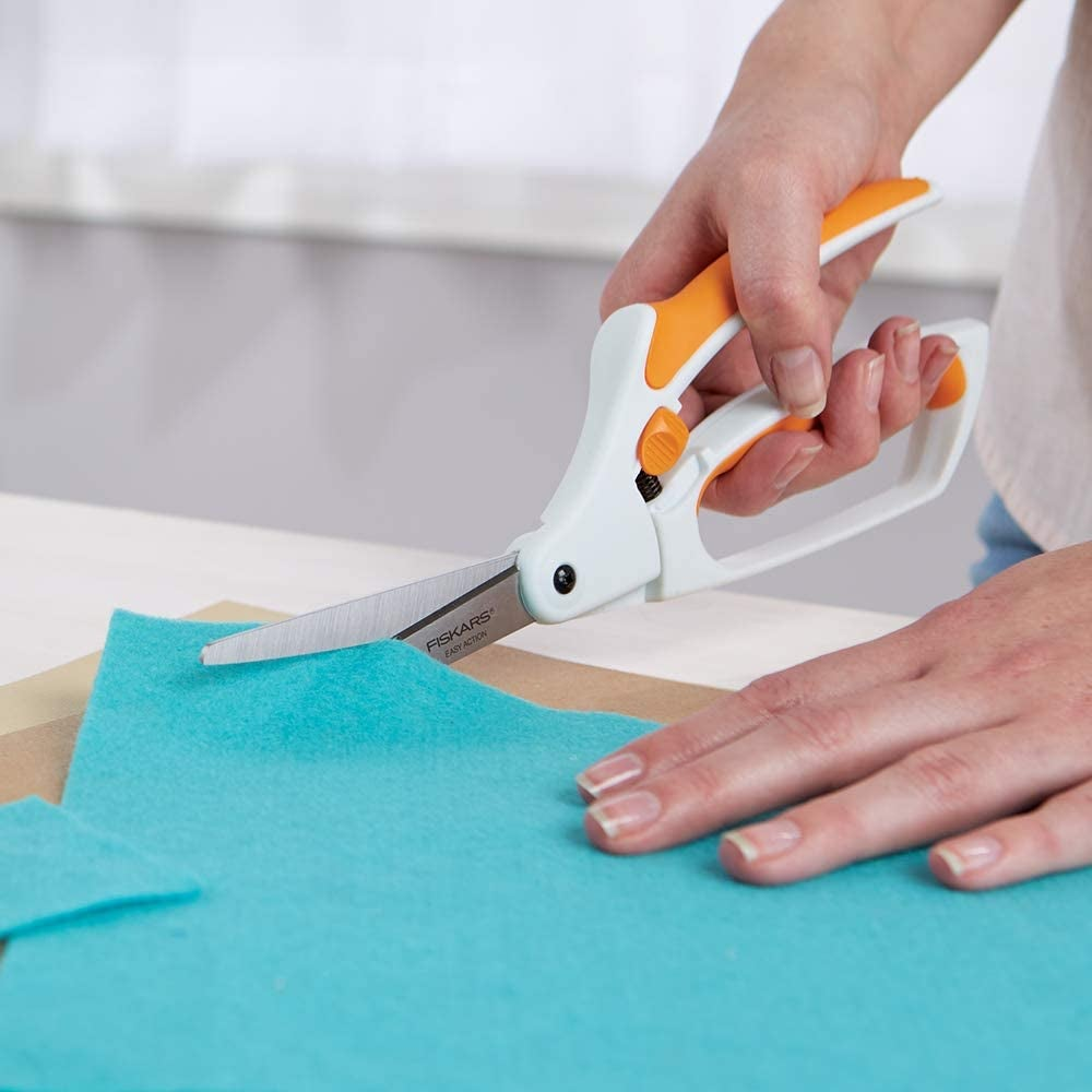 Model using white scissors with grip bottom and spring action top to cut a piece of fabric