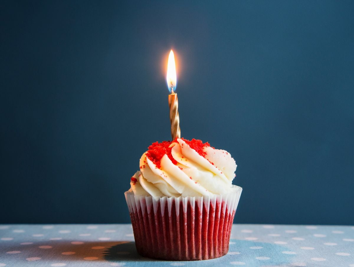 A red velvet cupcake with a candle in it