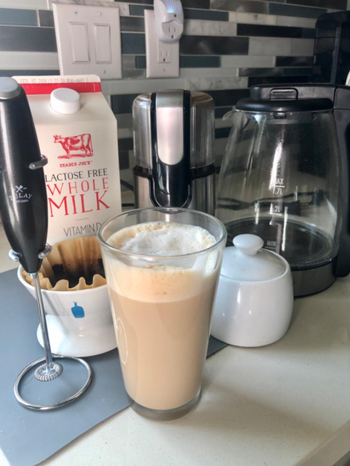 the milk frother next to a cup of coffee