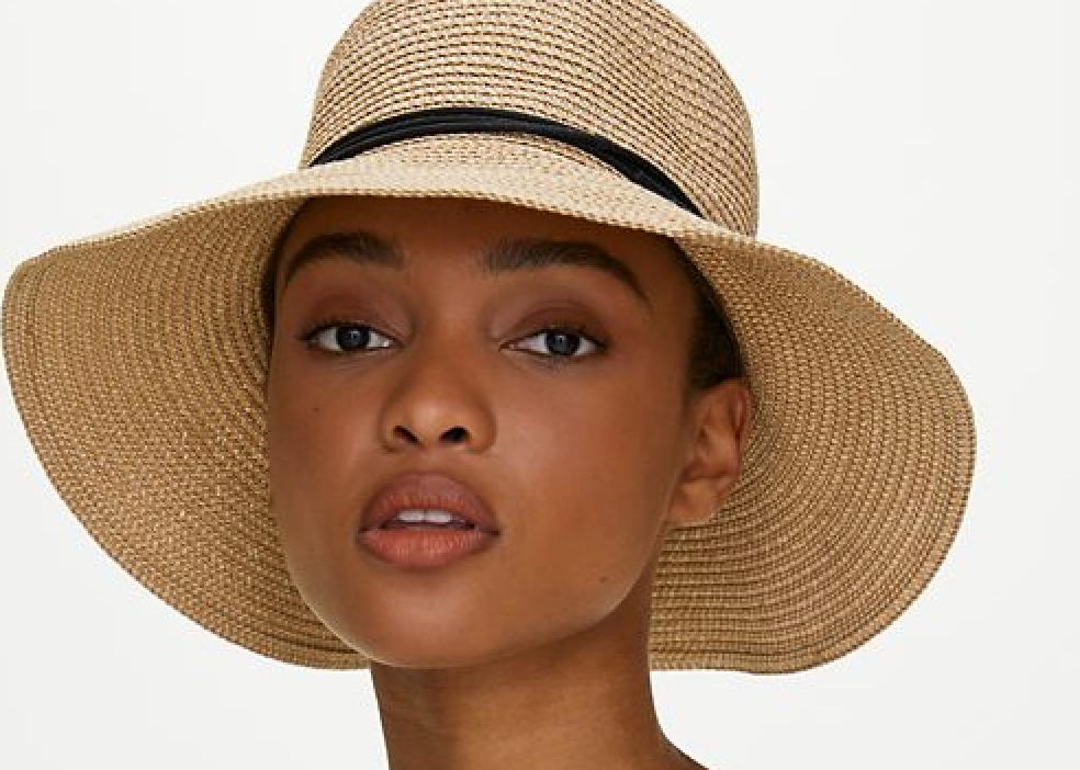 A woman is wearing a straw sun hat.