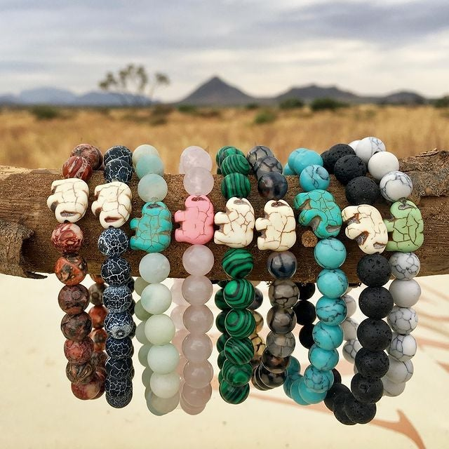 a line up of beaded bracelets in different colors each with an elephant charm