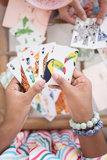 hands holding the cards painted with colorful animals like lions, tigers, zebras, and toucans