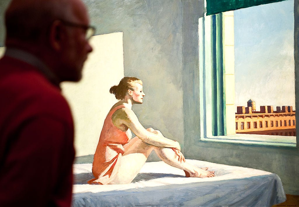 An Edward Hopper painting of a woman staring solemnly out of a window