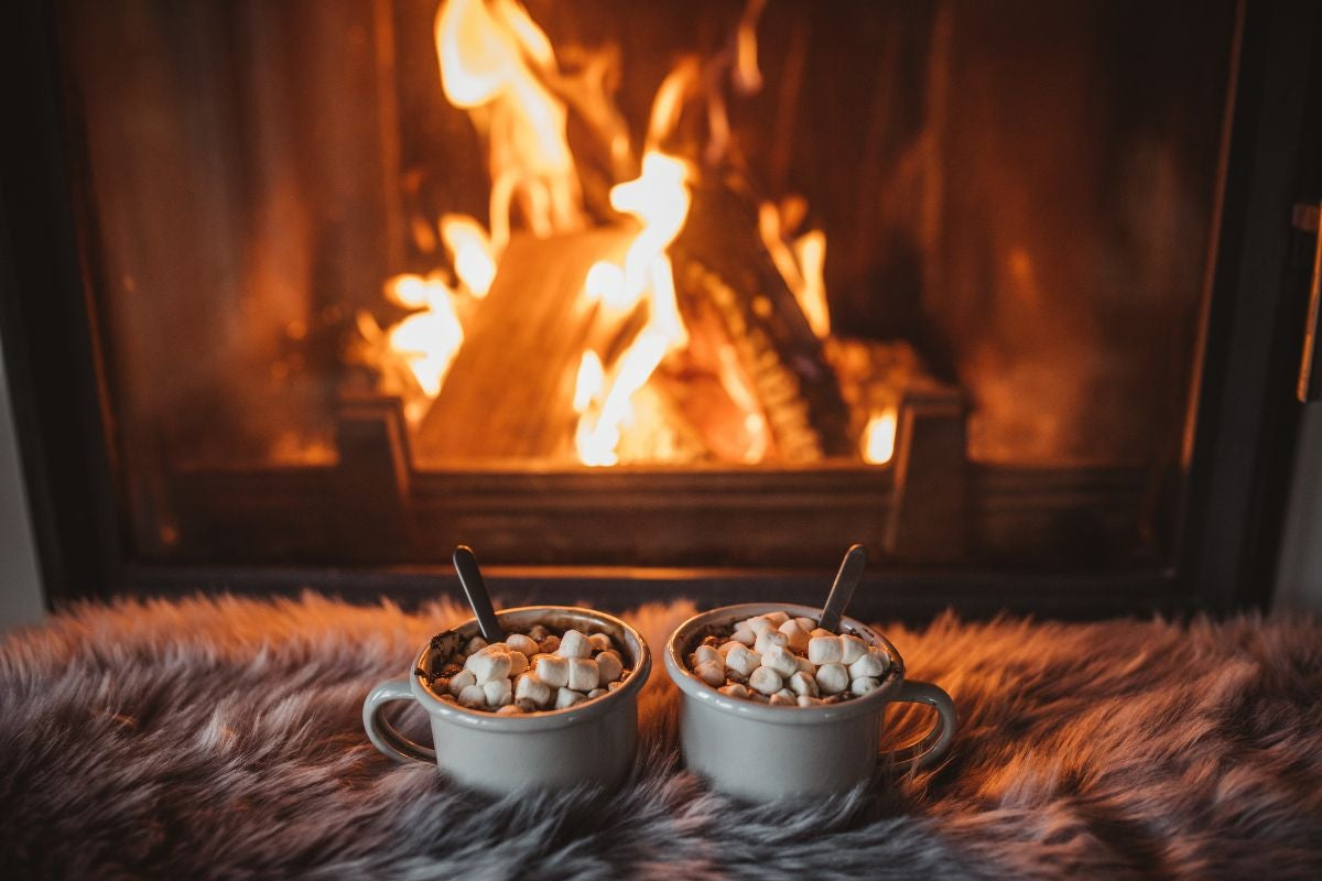 A fireplace with two mugs of hot chocolate and fluffy blanket in front of it