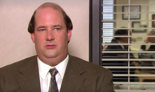 Kevin Malone is sitting at a chair with open blinds behind him