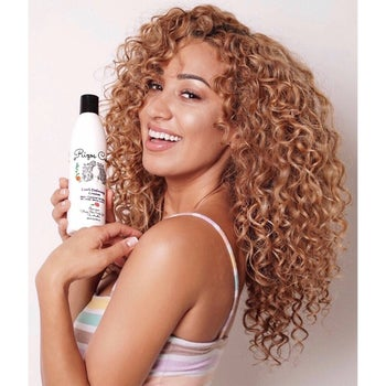 model with curly hair holding the bottle of curl defining cream