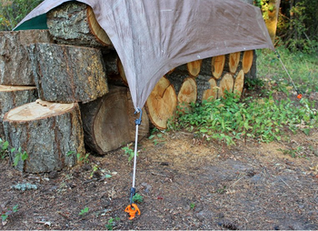 the ground screw anchoring a tarp over a pile of wood
